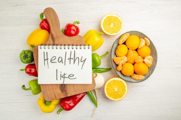 Vista de cima pimentões frescos com tangerinas no fundo branco salada dieta cor madura vida saudável