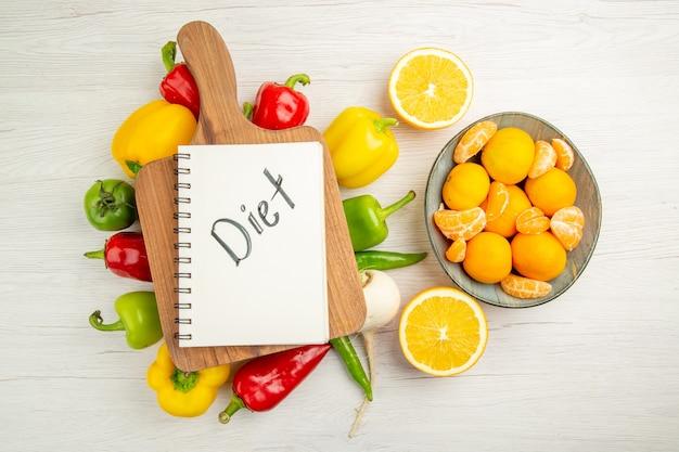 Vista de cima pimentões frescos com tangerinas no fundo branco salada foto colorida madura dieta saudável