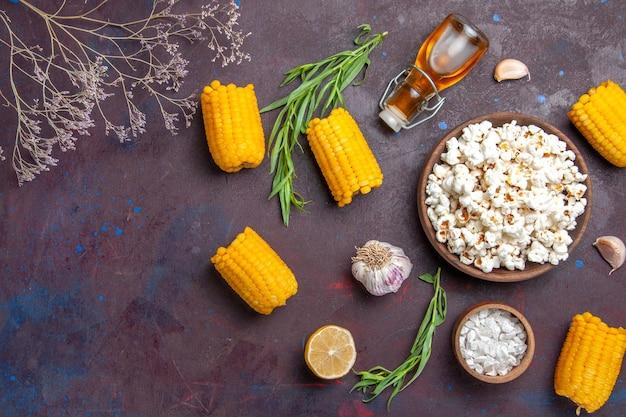 Vista de cima pipoca fresca com grãos amarelos crus em mesa escura e salgadinho de pipoca