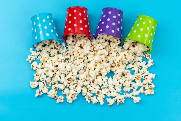 Vista de cima pipoca fresca dentro de cestos coloridos espalhados em azul, salgadinho de milho de cinema