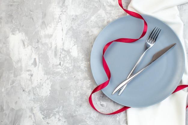 Vista de cima placa azul com garfo e faca na superfície clara refeição de vidro para senhoras na cozinha horizontal cor de comida