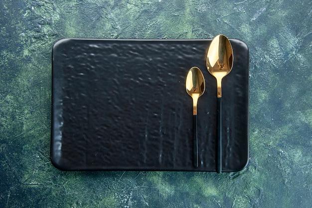 Vista de cima placa preta com colheres douradas sobre fundo azul escuro utensílio de comida cor jantar restaurante serviço refeição talheres