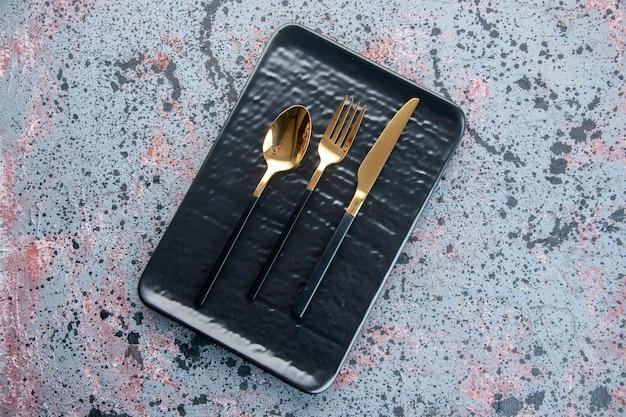 Vista de cima placa preta com talheres dourados na superfície clara serviço talheres jantar restaurante bandeja de comida cor