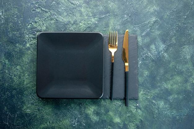 Vista de cima placa quadrada preta com faca dourada e garfo em um fundo escuro comida restaurante talheres jantar cozinha