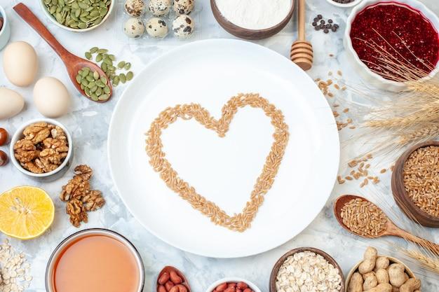 Vista de cima prato branco com ovos de geleia nozes e sementes diferentes na massa branca bolo cor doce foto biscoito açúcar torta de noz