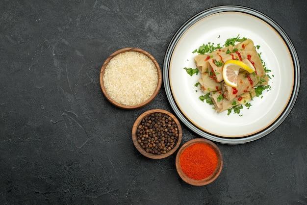Vista de cima prato branco com repolho recheado de comida com ervas, limão e molho no prato branco e tigelas de especiarias coloridas, pimenta preta e arroz no lado direito da mesa preta