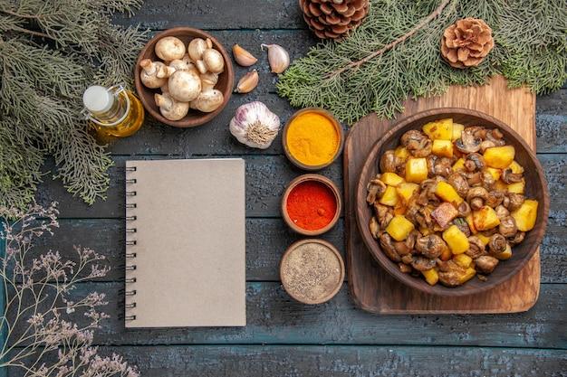 Vista de cima prato e prato de caderno de cogumelos e batatas na tábua ao lado de óleo de caderno de especiarias coloridas em garrafa tigela de alho de cogumelos e ramos com cones