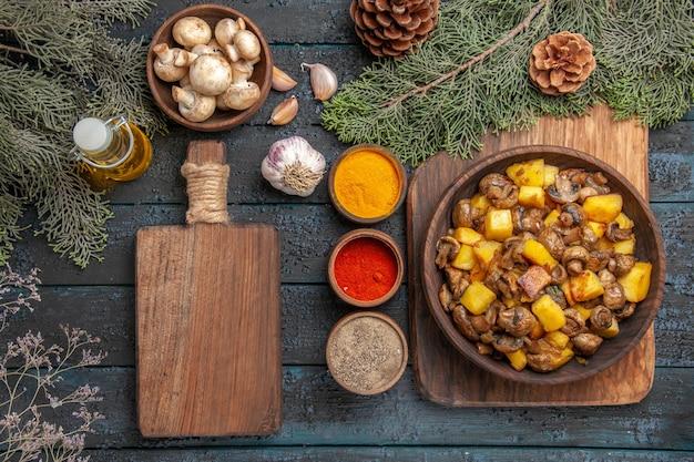 Vista de cima prato e prato de cogumelos e batatas na placa de madeira ao lado de especiarias coloridas, óleo de tábua de corte em garrafa tigela de alho de cogumelos e ramos com cones