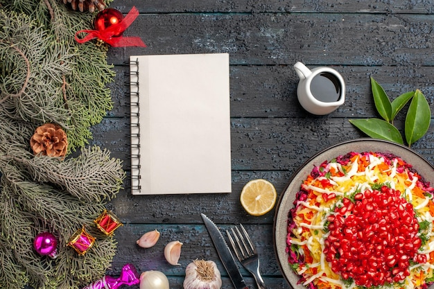 Vista de cima prato e ramos de abeto apetitoso prato de natal com alho e limão tigela de óleo ao lado da faca de garfo de caderno branco e ramos de abeto com cones