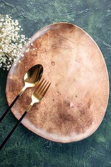 Vista de cima prato marrom com colher dourada e garfo na superfície escura jantar talheres refeição comida restaurante utensílio tabela cor
