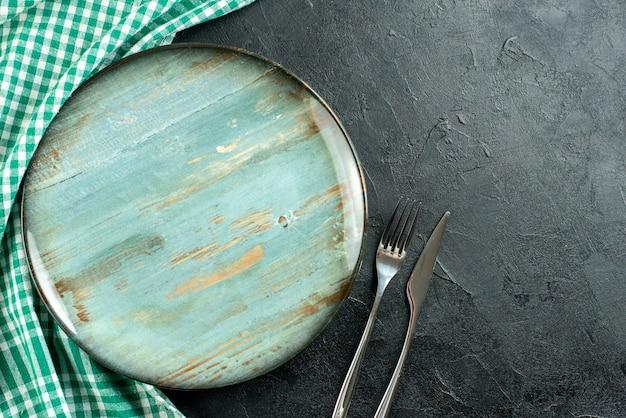 Vista de cima, prato redondo, garfo e faca toalha de mesa verde e branca no espaço preto da mesa