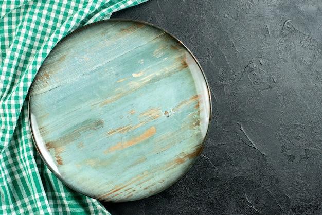 Vista de cima prato redondo toalha de mesa verde e branca em mesa preta com espaço livre