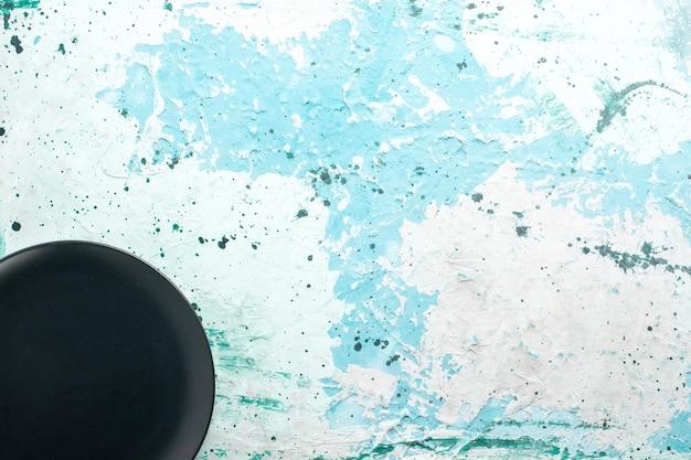 Vista de cima prato redondo vazio de cor escura no fundo azul claro prato de cozinha talheres de vidro