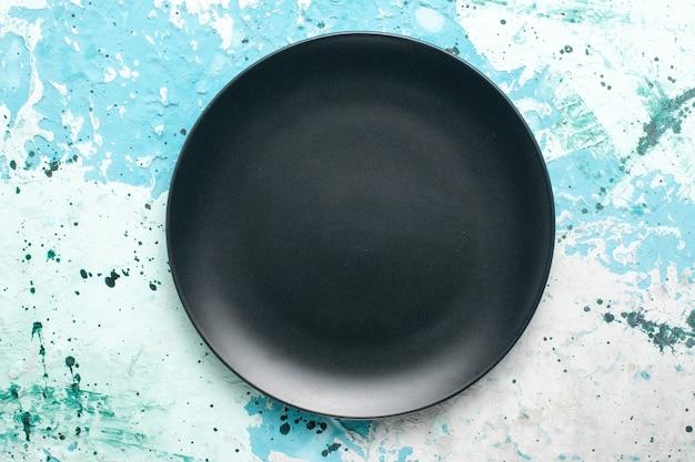 Vista de cima prato redondo vazio de cor escura no fundo azul prato de cozinha talheres de vidro