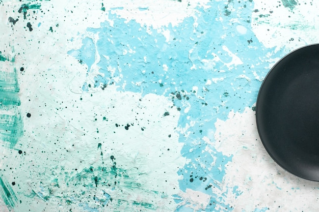 Vista de cima prato redondo vazio de cor escura sobre fundo azul prato de cozinha talheres