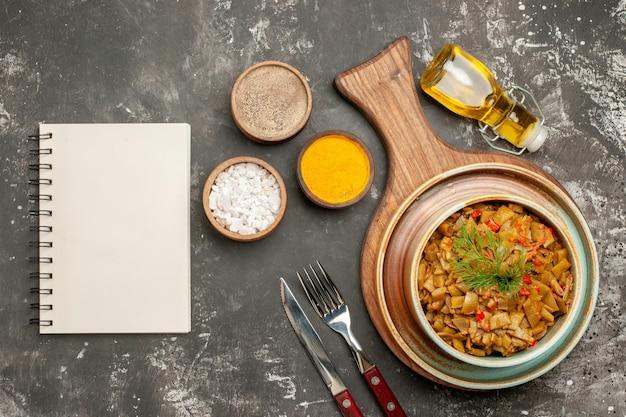 Vista de cima prato saboroso prato de feijão verde com tomate ao lado da faca de garfo, garrafa de caderno branco de óleo e três tipos de especiarias na mesa escura