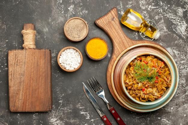 Vista de cima prato saboroso prato de feijão verde com tomate no quadro ao lado da garrafa de faca de garfo de óleo e três tipos de especiarias na mesa escura
