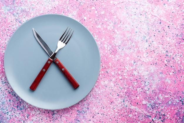 Vista de cima prato vazio de cor azul com garfo e faca na parede rosa prato de foto colorida talheres de comida