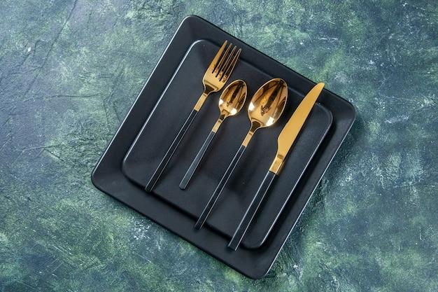 Vista de cima pratos escuros com colheres douradas garfo e faca na superfície azul escuro alimentos talheres cor café cozinha restaurante escuridão