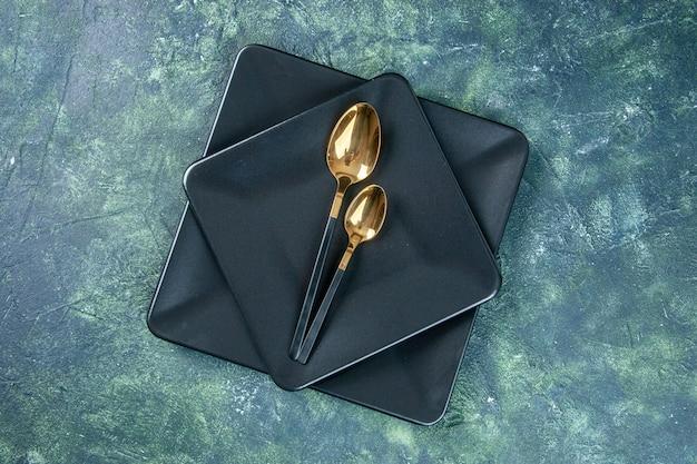Vista de cima pratos pretos com colheres douradas sobre fundo escuro alimentos talheres restaurante jantar café