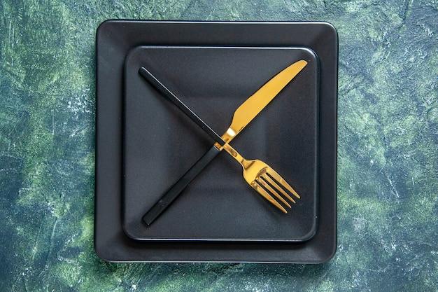 Vista de cima pratos pretos com garfo e faca dourados cruzados na superfície escura.