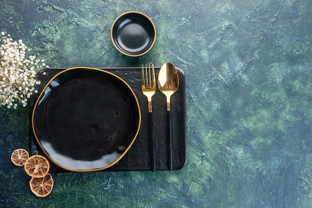 Vista de cima pratos pretos com talheres dourados sobre fundo escuro refeição jantar prata restaurante serviço talheres comida