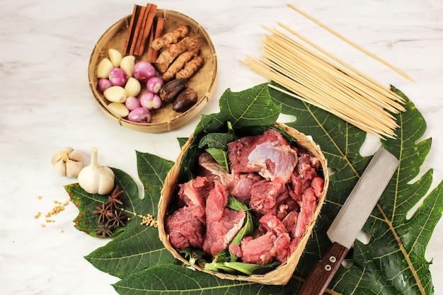 Vista de cima preparação dos ingredientes fazendo satay de cordeiro (sate kambing), carne de cordeiro crua com folha de mamão para tornar a carne suculenta e macia, menu para eid al adha