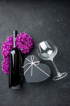 Vista de cima presente de dia dos namorados com flores e garrafa de vinho em fundo escuro amor casal presente cor álcool casamento