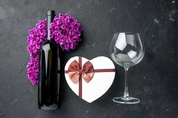 Vista de cima presente de dia dos namorados com flores e garrafa de vinho no fundo escuro. amor sentindo casal presente cor álcool