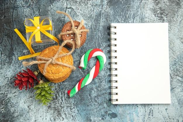 Vista de cima presentes de natal amarrados biscoitos doces de natal um caderno na superfície cinza