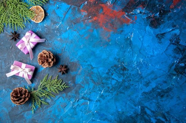 Vista de cima presentes de natal ramos de árvore de abeto cones anis na superfície azul