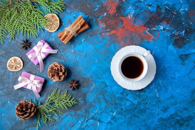 Vista de cima presentes de natal ramos de árvore de abeto cones anis xícara de chá na superfície azul