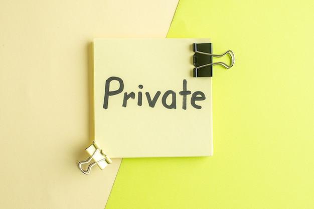 Vista de cima privada nota escrita sobre fundo verde-amarelo trabalho escritório escola caderno de negócios salário cor dinheiro faculdade