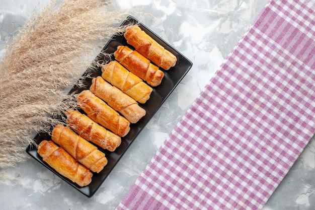 Vista de cima pulseiras deliciosas assadas dentro de bolor preto na mesa cinza-claro pastelaria doce e bolo de açúcar