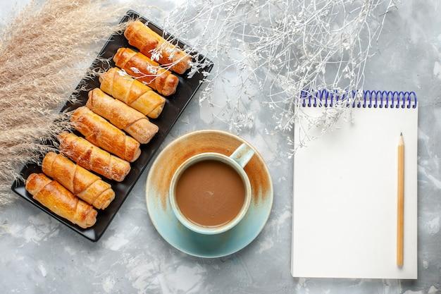 Vista de cima pulseiras deliciosas com leite, café e bloco de notas na mesa cinza, bolo, biscoito, doce, açúcar