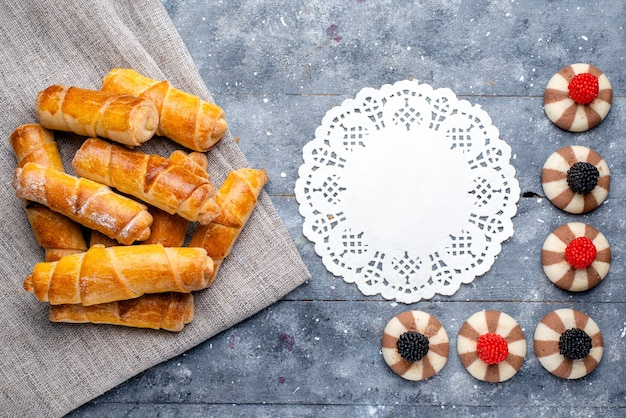 Vista de cima pulseiras deliciosas com recheio junto com biscoitos no fundo cinza bolo assar biscoito doce