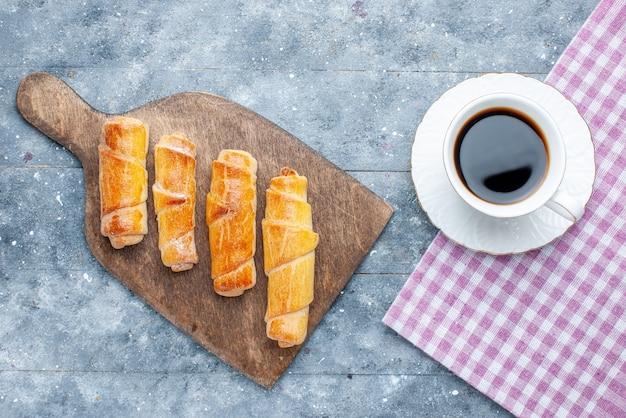 Vista de cima, pulseiras deliciosas e doces com recheio e uma xícara de café na mesa de madeira cinza.