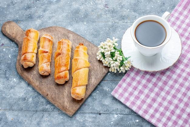 Vista de cima, pulseiras deliciosas e doces com recheio, juntamente com uma xícara de café com flores brancas na mesa de madeira cinza