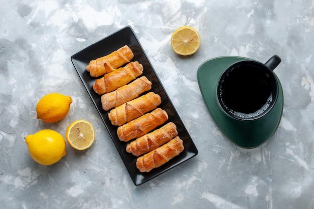 Vista de cima pulseiras doces com uma xícara de chá de limão na mesa de luz, bolo de confeitaria asse açúcar doce