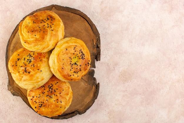 Vista de cima, qogals assados redondos em formato saboroso e recém saído do forno na mesa de madeira marrom