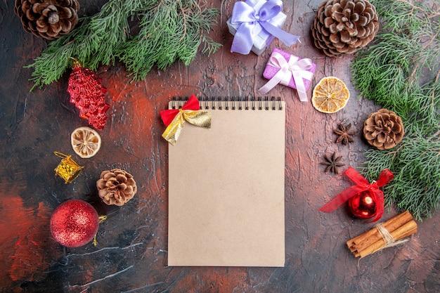 Vista de cima ramos de pinheiro com cones, anis, canela, presentes e pingentes, um caderno, fundo, vermelho escuro, foto natal
