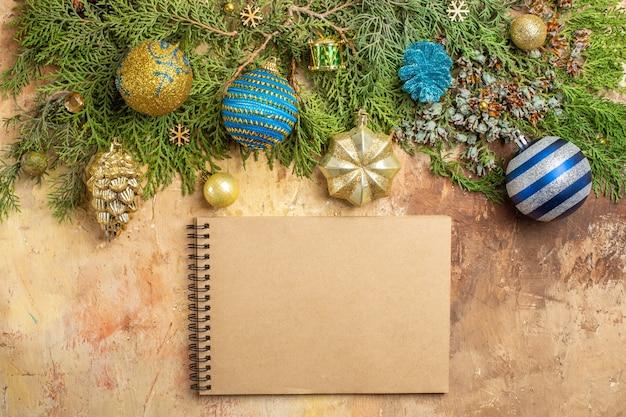 Vista de cima ramos de pinheiro enfeites de árvore de natal um caderno em fundo bege