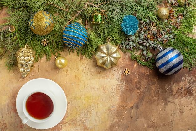 Vista de cima ramos de pinheiro enfeites de árvore de natal, uma xícara de chá em fundo bege