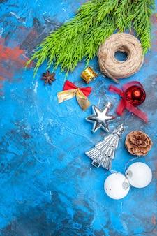 Vista de cima ramos de pinheiro fio de palha brinquedos de árvore de natal sementes de anis em fundo azul-vermelho