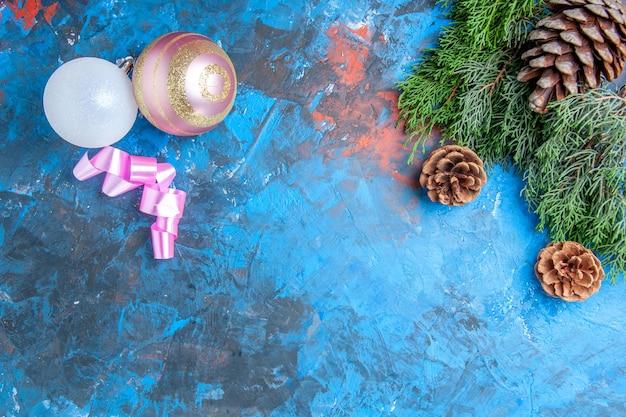 Vista de cima ramos de pinheiro pinhas bolas de árvore de natal na superfície azul-vermelha