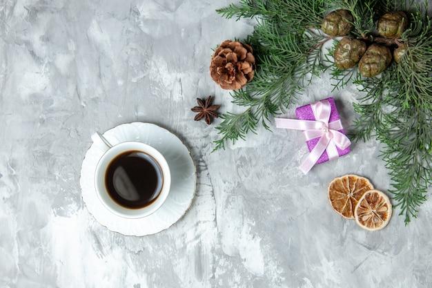 Vista de cima ramos de pinheiro xícara de chá rodelas de limão secas na superfície cinza