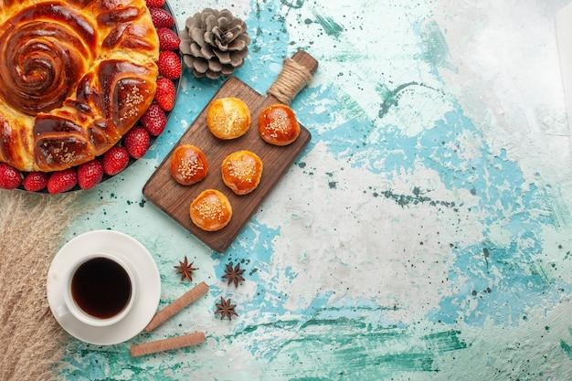 Vista de cima redonda deliciosa torta com bolinhos de morango e uma xícara de chá na superfície azul claro
