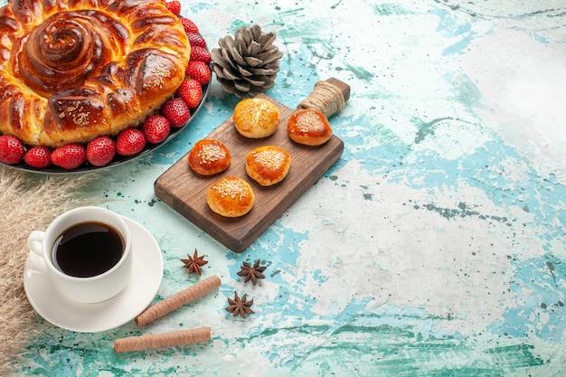 Vista de cima redonda deliciosa torta com morangos e xícara de chá em uma superfície azul clara