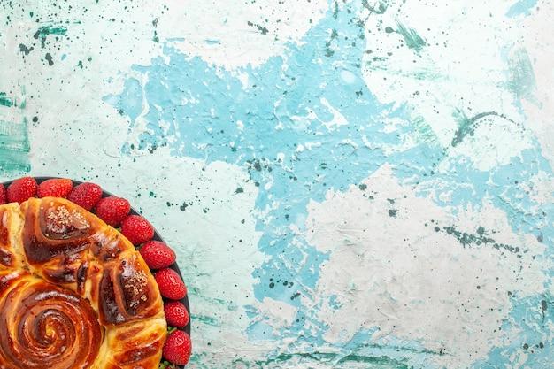 Vista de cima redonda deliciosa torta com morangos vermelhos frescos na superfície azul