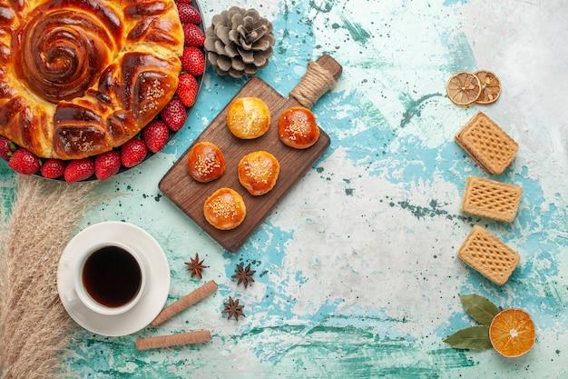Vista de cima redonda deliciosa torta com waffles de morango e xícara de chá na superfície azul claro